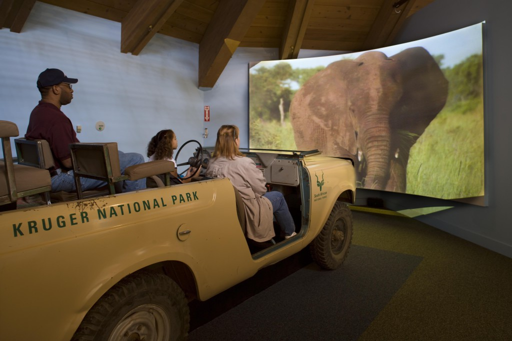 Three people on a jeep with an elephant projected onto a screen in front of them