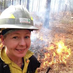 Woman posing with a hard hat next to a flame