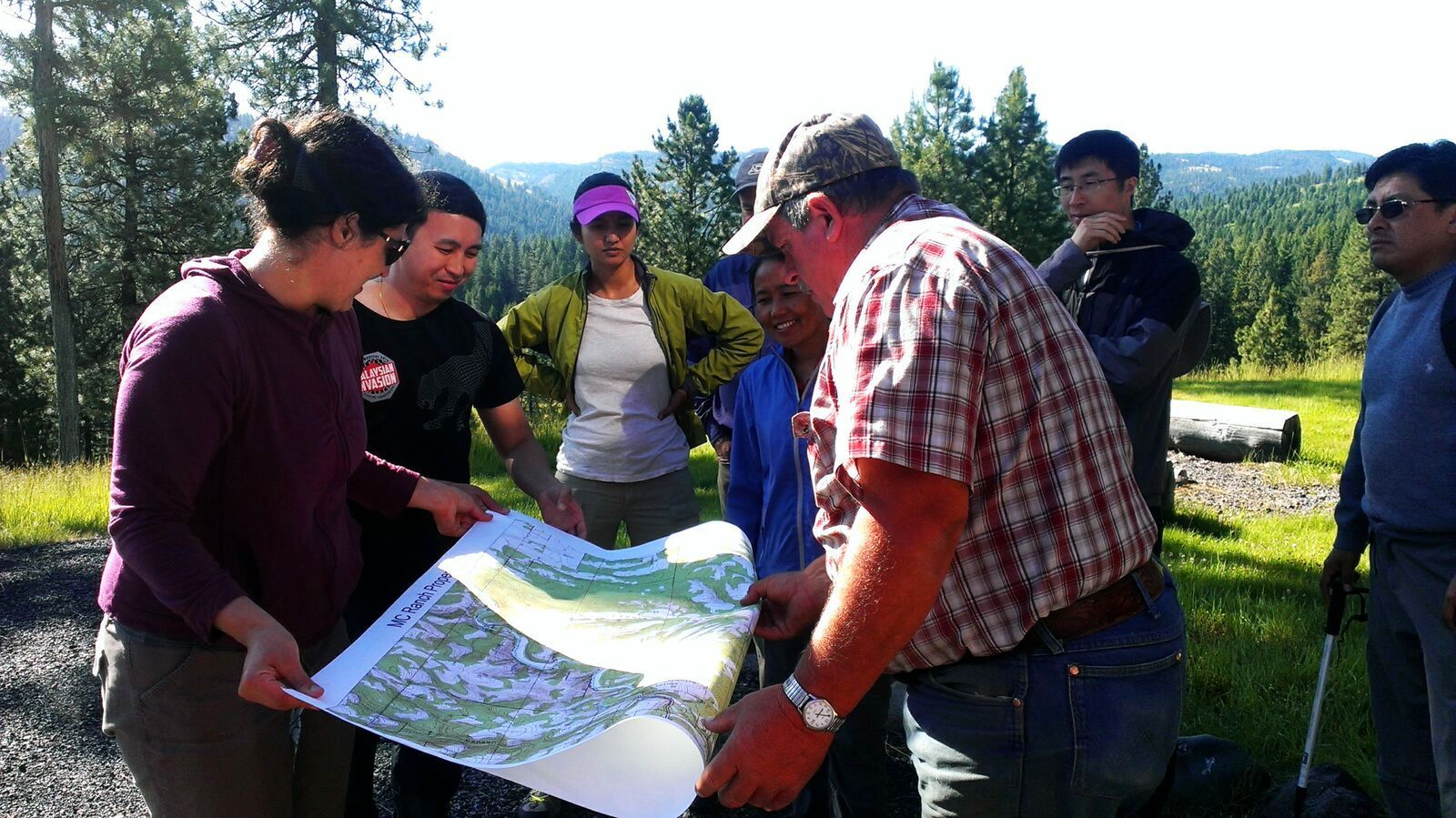 International Fellows examine a map on a trail