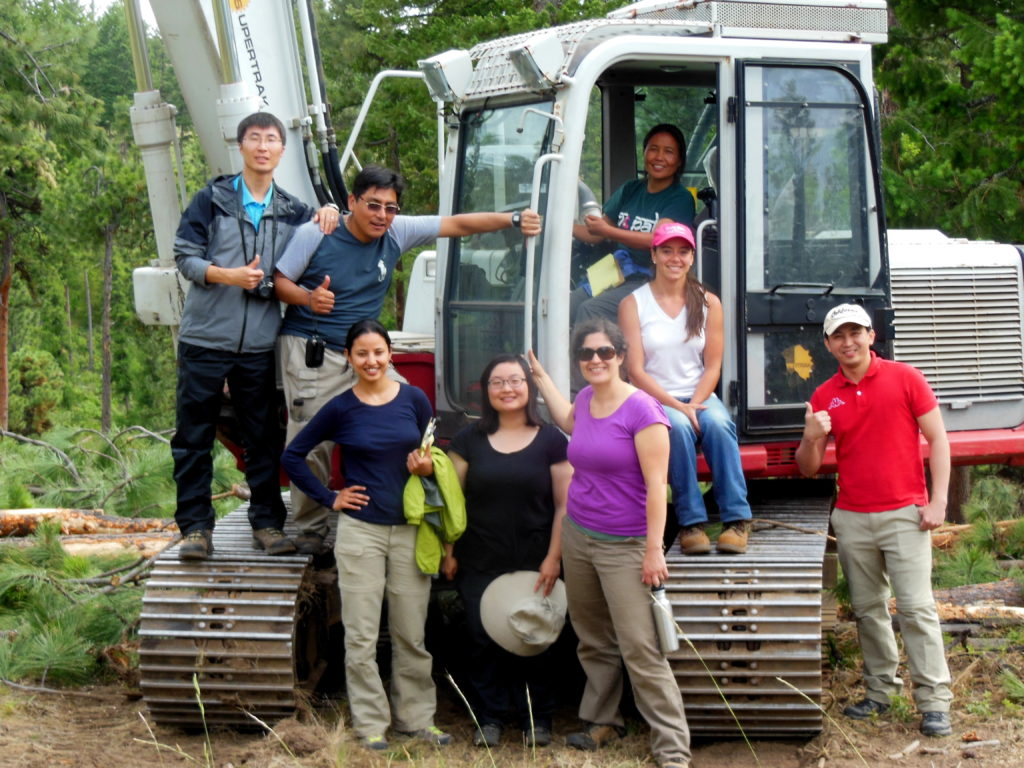 A group of International Fellows pose on an excavator for a photo.