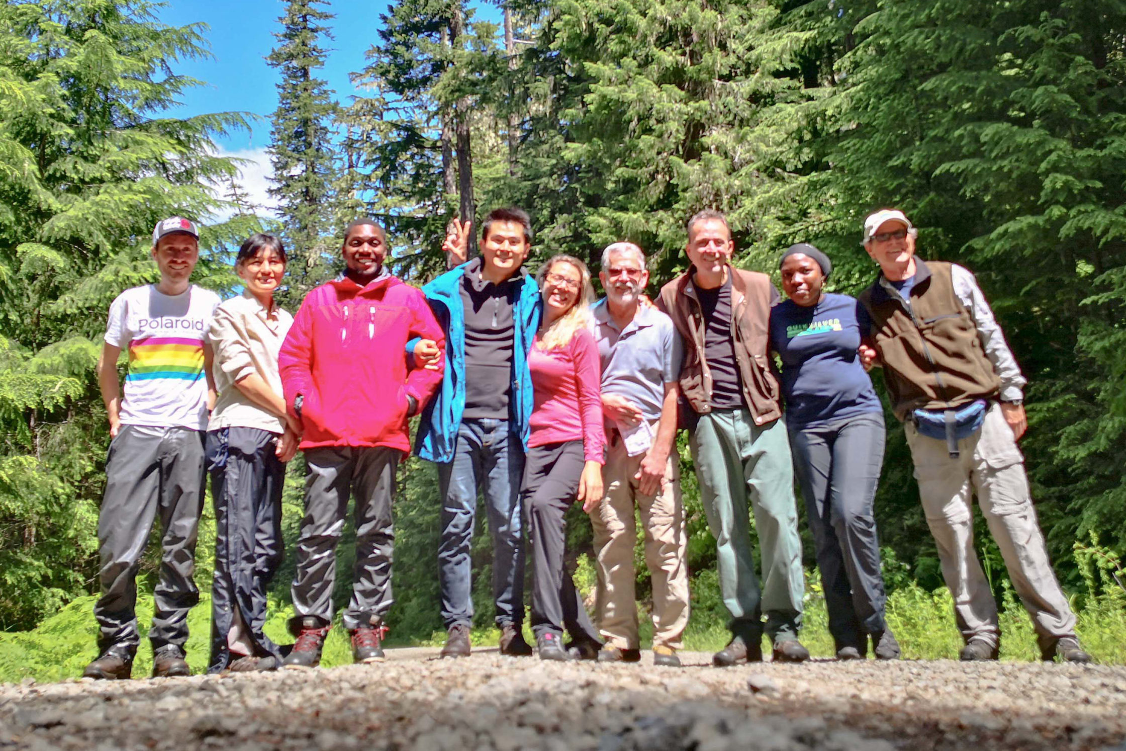 International Fellows posing on a trail in a forest