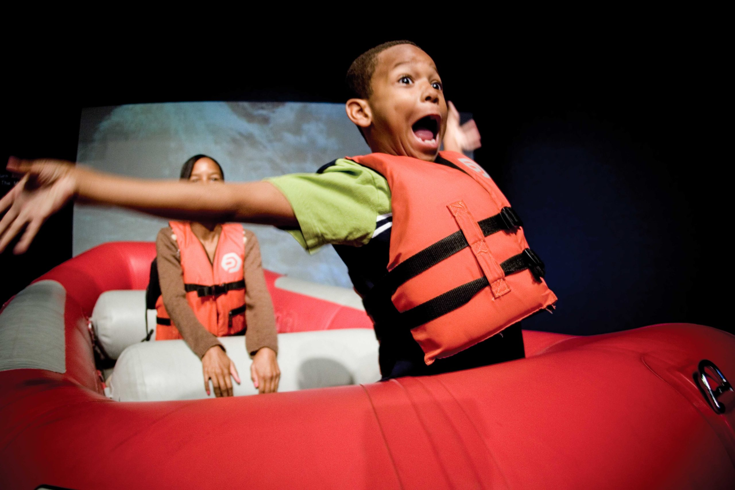 Excited young boy with life jacket on raft