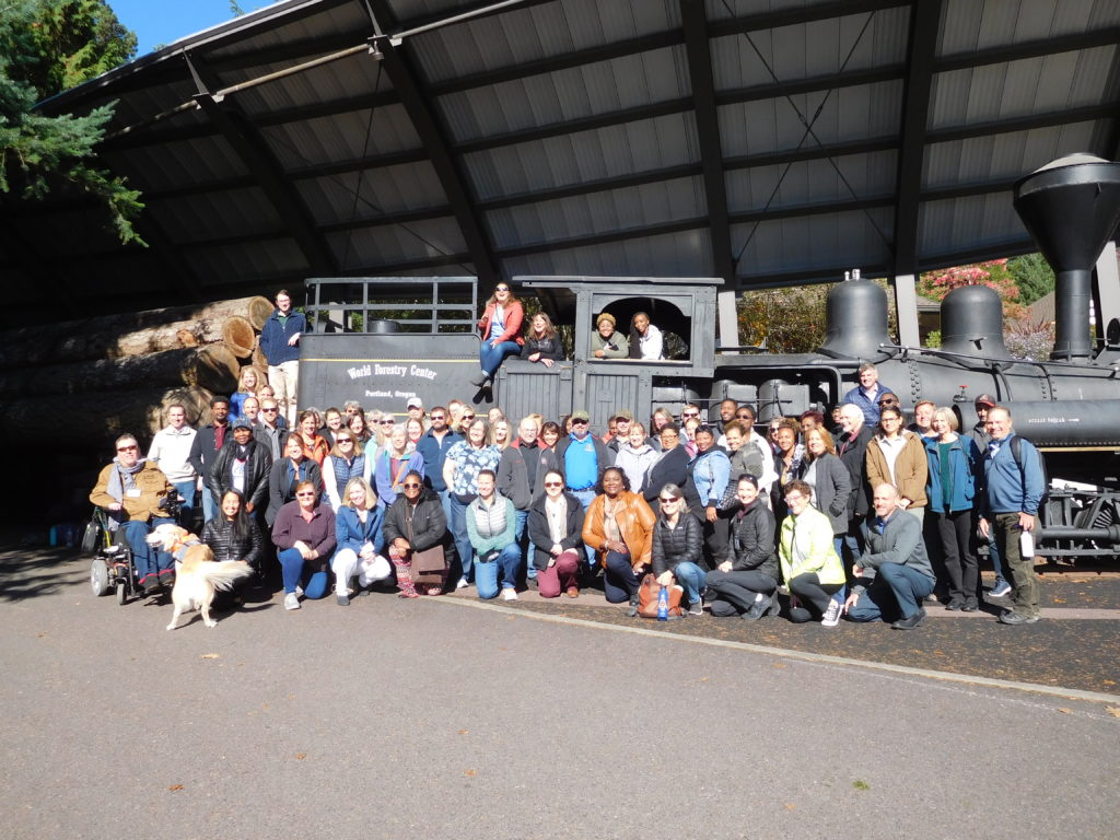 Group of people poses for a photo in front of Peggy the Train.