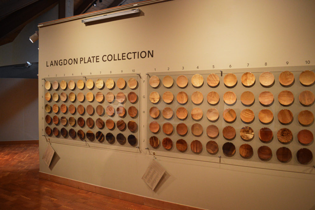 Some of the 150 wooden plates on a wall, showcasing the Langdon Plate Collection.