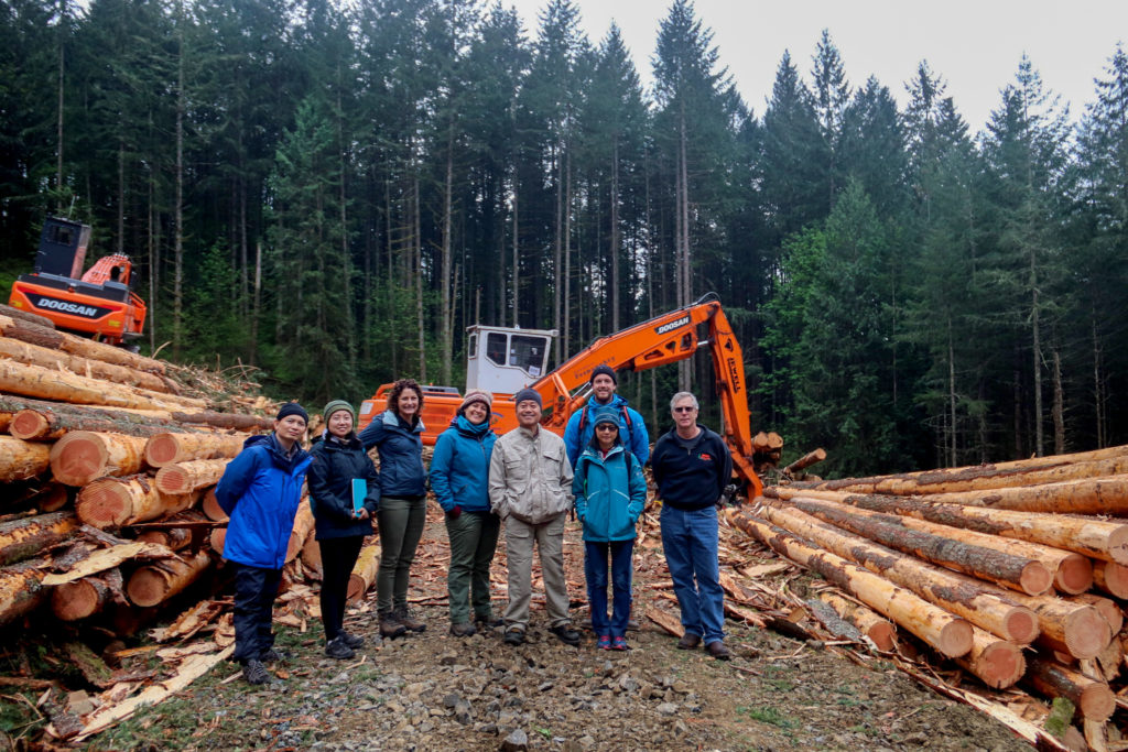 A group of International Fellows pose between stacks of timber for a picture.