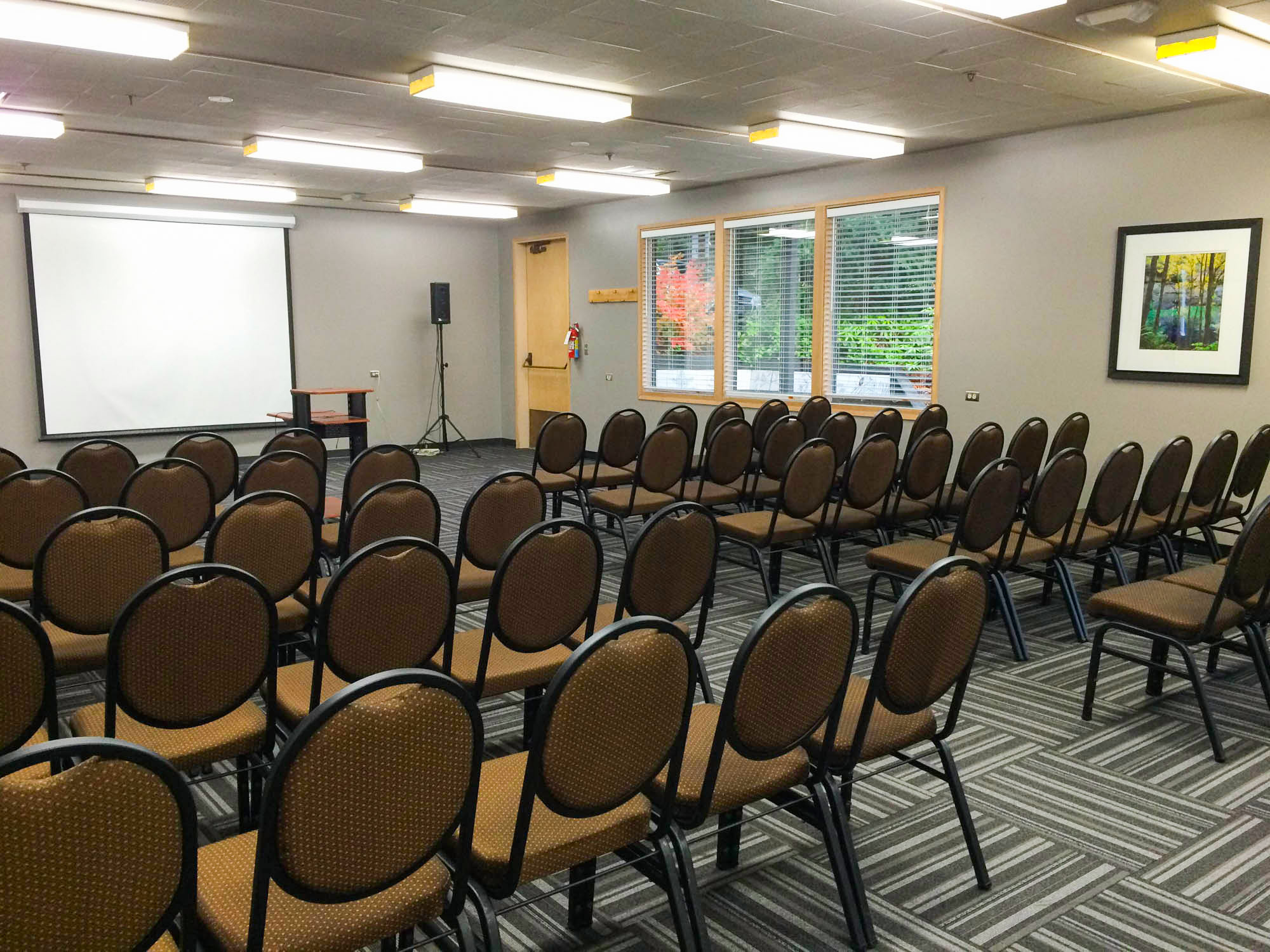 Conference room set up with chairs and projector screen