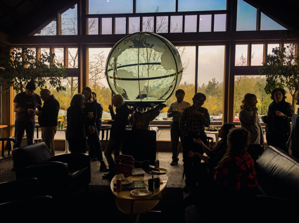 A group of people socialize before a large globe statue and windows
