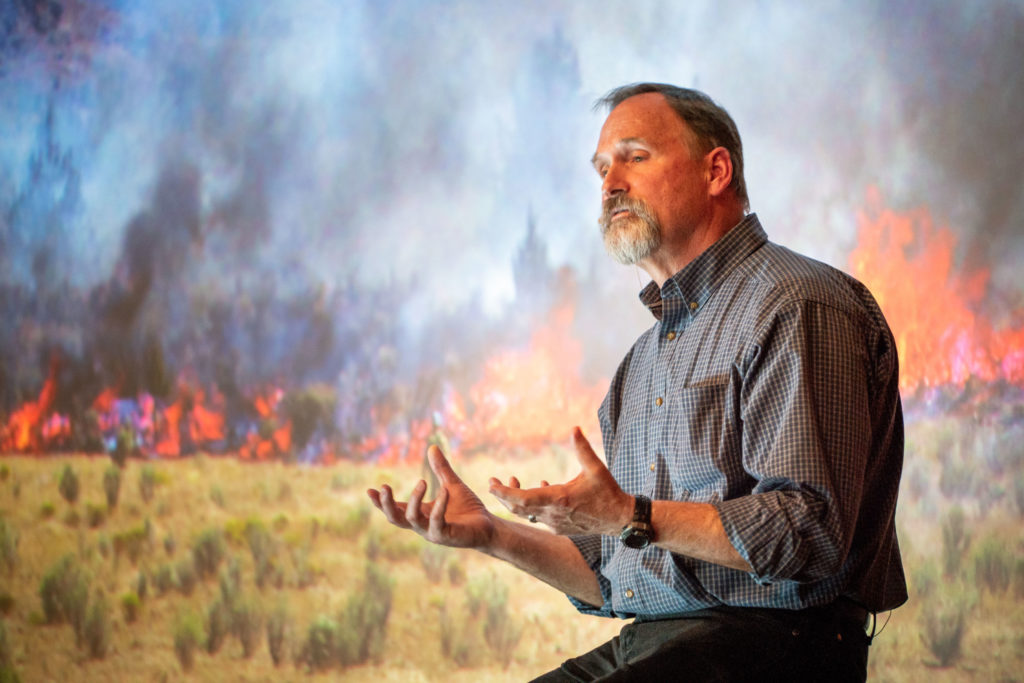 Man talking with forest fire background.