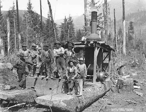 Loggers pose next to the steam donkey machine.
