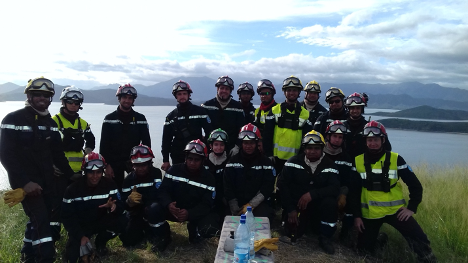 Group photo of Romain and his trainees posing in front of a body of water.